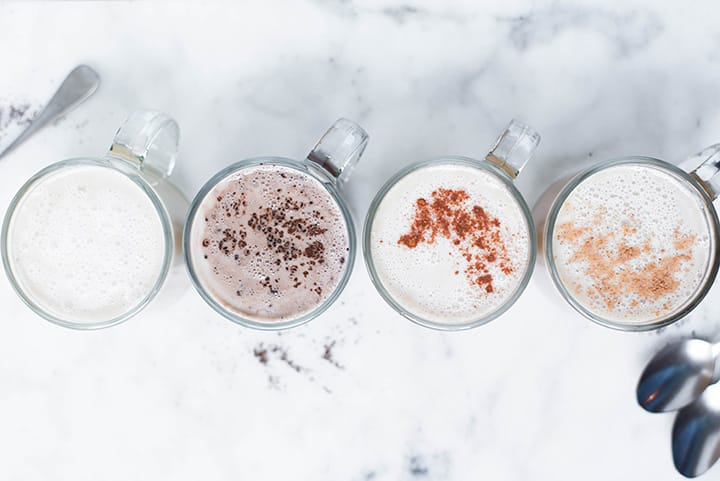 Top view of the 4 homemade lattes including eggnog latte, chai latte, vanilla latte, and mocha latte in mugs, garnishes and ready to be served.