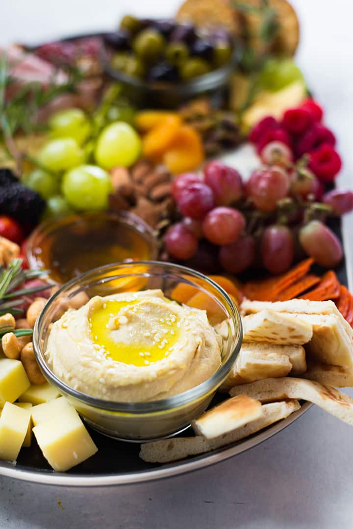 Side view of the Port Wine, Meat and Cheese Platter with a closeup on the hummus dip and pita bread as a sampling of some of the Top Anti-Inflammatory Foods.