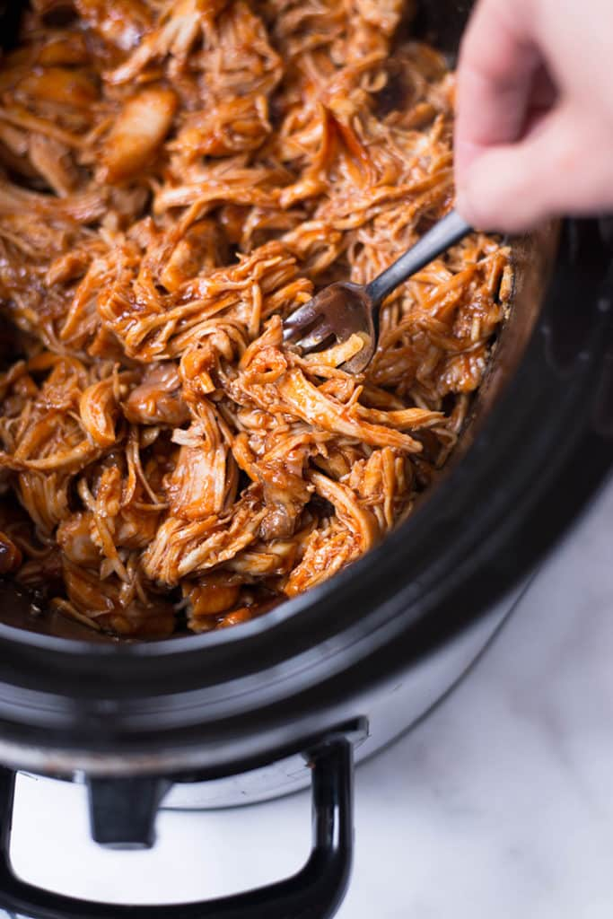 Overhead view of the slow cooker containing shredded chicken for the Shredded Chicken Meal Prep recipes.
