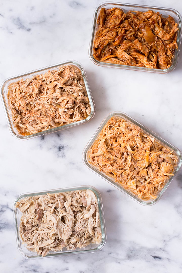View from the top of 4 meal prep containers filled with shredded chicken including a simple garlic and olive oil slow cooker shredded chicken, Slow Cooker Mexican Shredded Chicken, Slow Cooker BBQ Shredded Chicken, and Slow Cooker Buffalo Shredded Chicken.