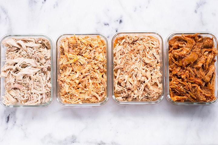 Horizontal image with a view from the top of the prepped shredded chicken. The shredded chicken is stored in meal prep containers.