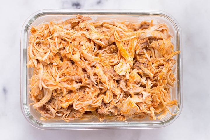 Slow Cooker Buffalo Shredded Chicken in a meal prep container.