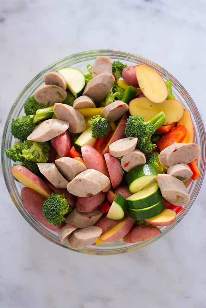 Overhead view of an ideal meal for intermittent fasting,including sausage, broccoli, zucchini, bell pepper, and red potatoes in a bowl.