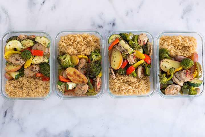 4 meal prep containers filled with Sheet Pan Sausage and Veggies and quinoa.