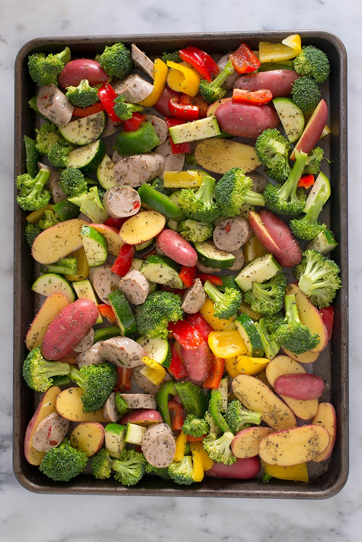 The sausage and vegetables for Sheet Pan Sausage and Veggies recipe seasoned with olive oil, salt, pepper, basil, thyme, oregano, and garlic powder placed in a baking sheet.