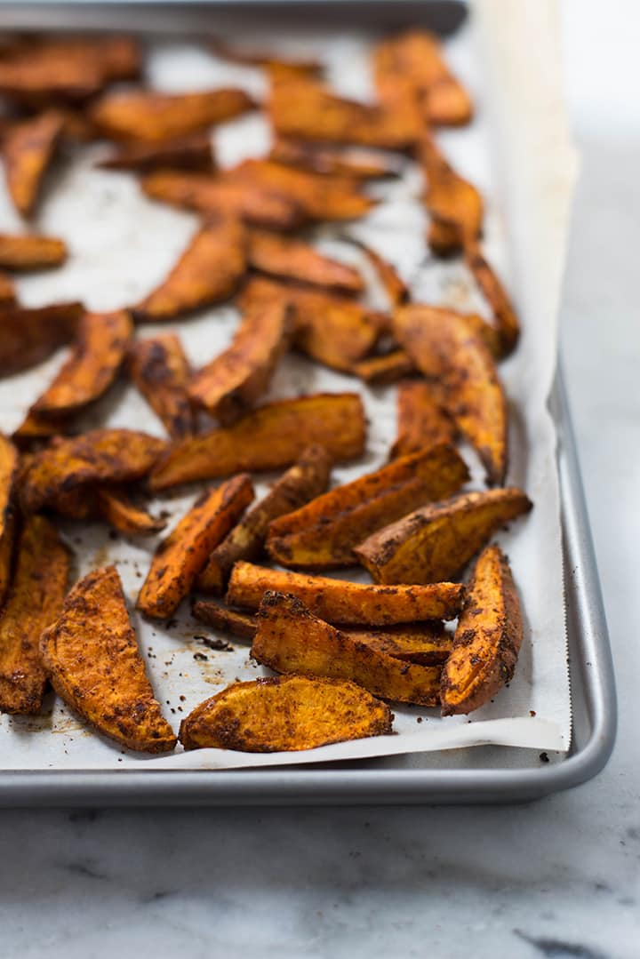 Close up of sweet potato fries on a baking sheet.