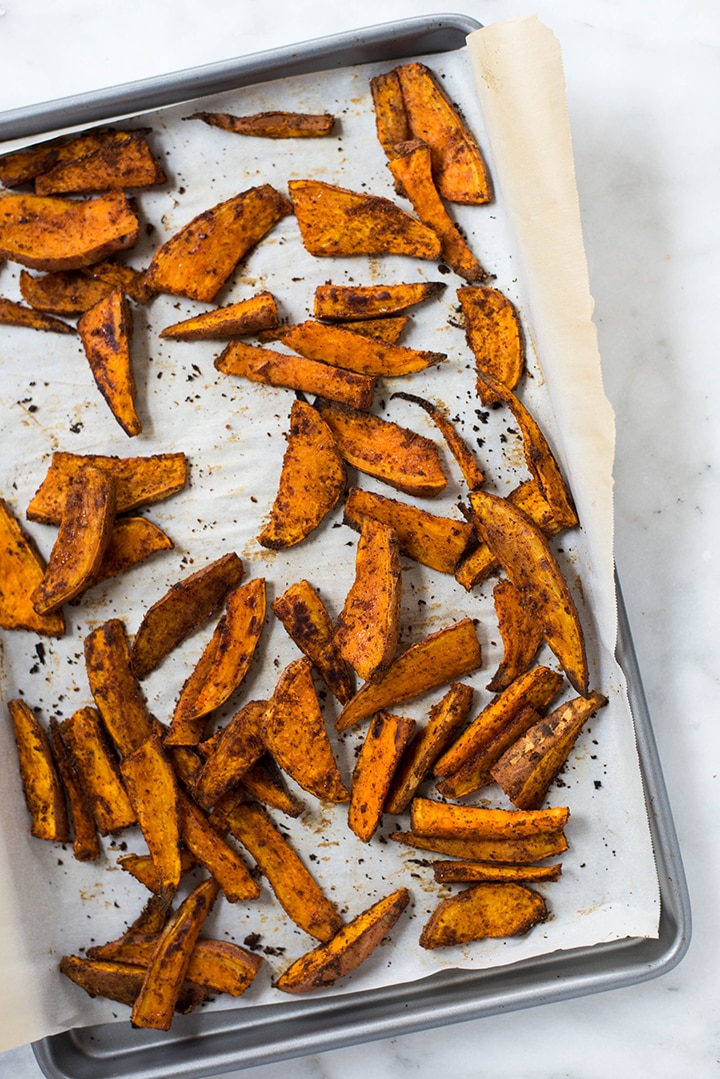 Top view of freshly baked sweet potato fries spread on a baking sheet.