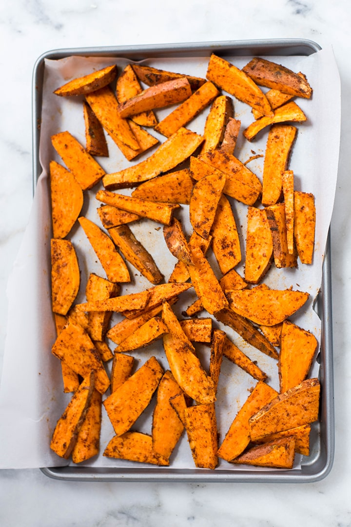 Sweet potato wedges on a baking sheet right before they will be transferred to the oven to bake.