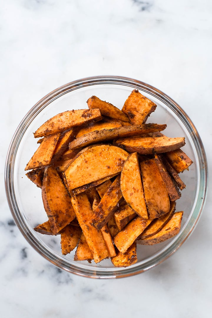 Top view of a bowl of sweet potato fries seasoned and ready to be transferred to the baking sheet and baked in the oven.