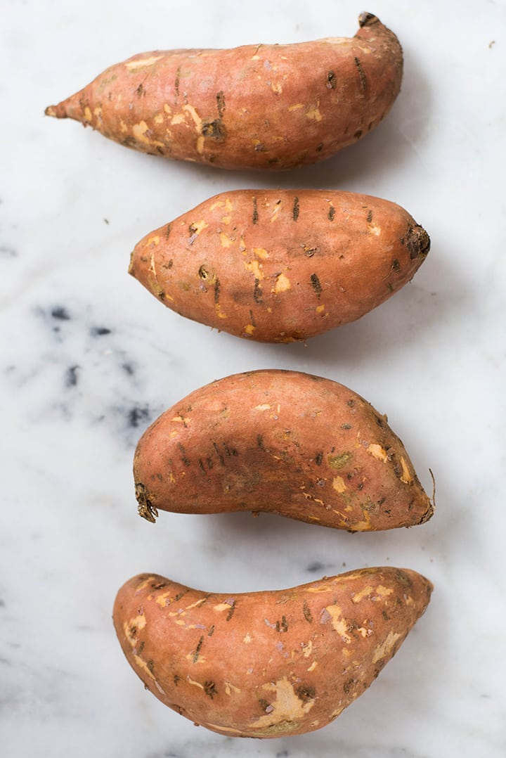 4 raw sweet potatoes ready to be turned into sweet potato fries.