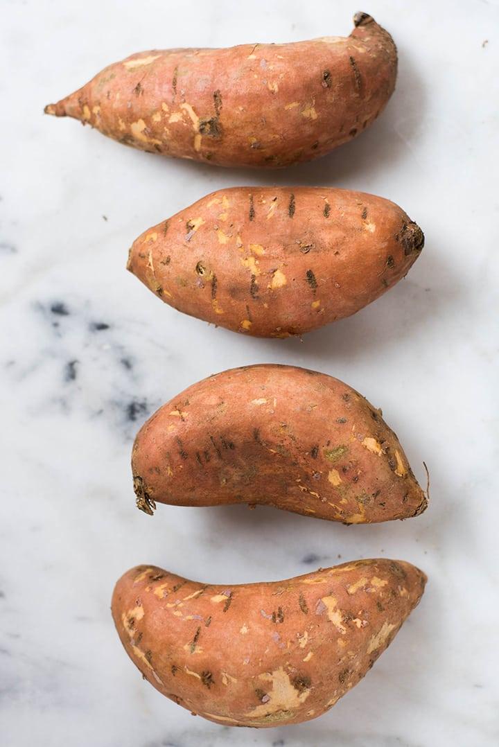 4 raw sweet potatoes ready to be turned into sweet potato fries.