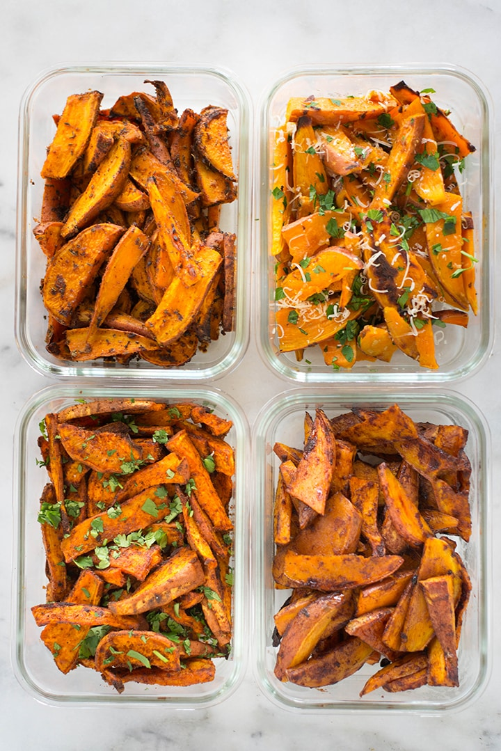 Top view of 4 meal prep containers filled with sweet potato fries. The flavors are: garlic& herbs, spicy chile, cajun, and cinnamon sugar.