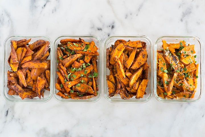 Horizontal image of meal prep containers filled with 4 different flavors of sweet potato fries including garlic & herbs, spicy chile, cajun, and cinnamon sugar.