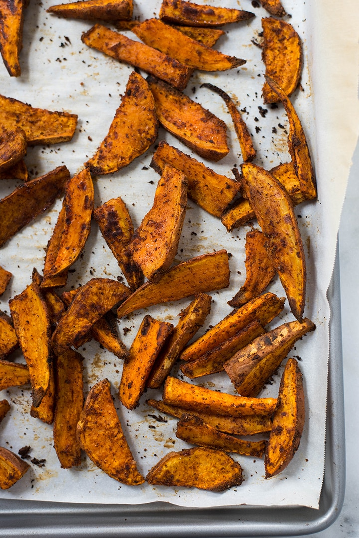 Top view of freshly baked sweet potato fries on a baking sheet.