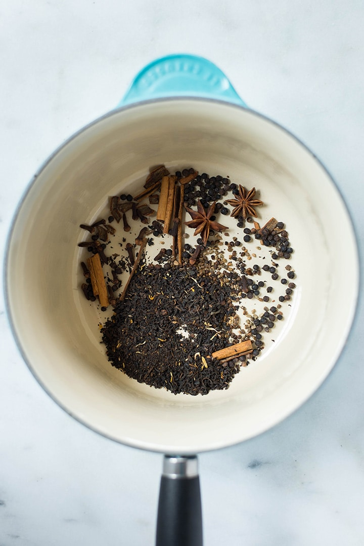 Spices for chai latte including cinnamon sticks, black peppercorns, star anise, cloves, cardamon, and fresh ginger in a saucepan.