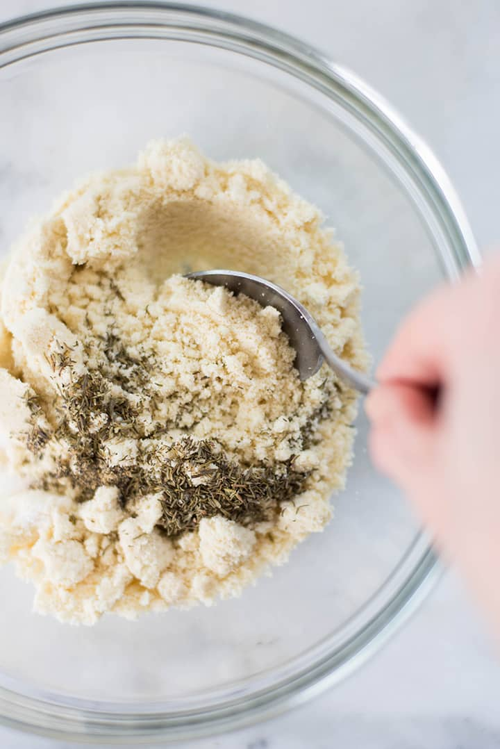 Mixing almond meal with salt, pepper, olive oil, and thyme to replace the bread crumbs in the stuffing for baked mushrooms.