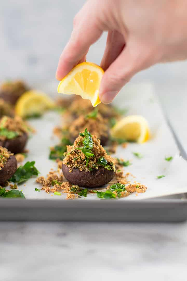 Squeezing lemon juice over the garlic stuffed mushrooms.