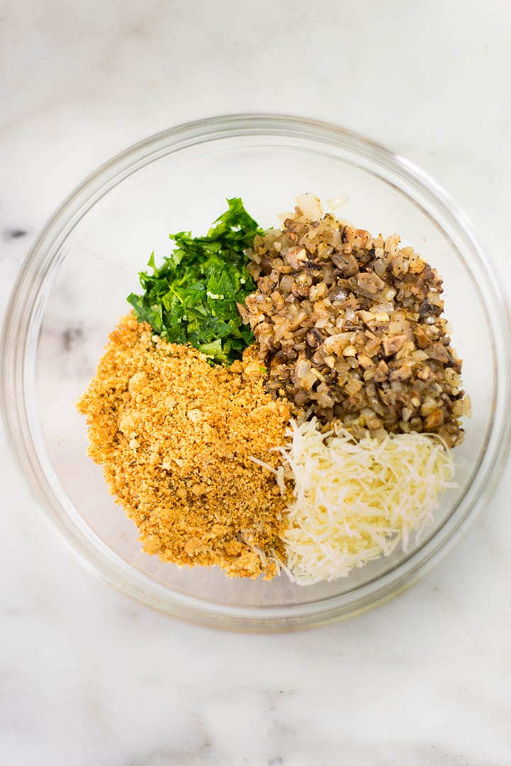 Stuffing ingredients for the garlic stuffed mushrooms in separate piles in a mixing bowl. The ingredients include baked almond meal, parmesan,parsley, and cooked mushrooms stems.