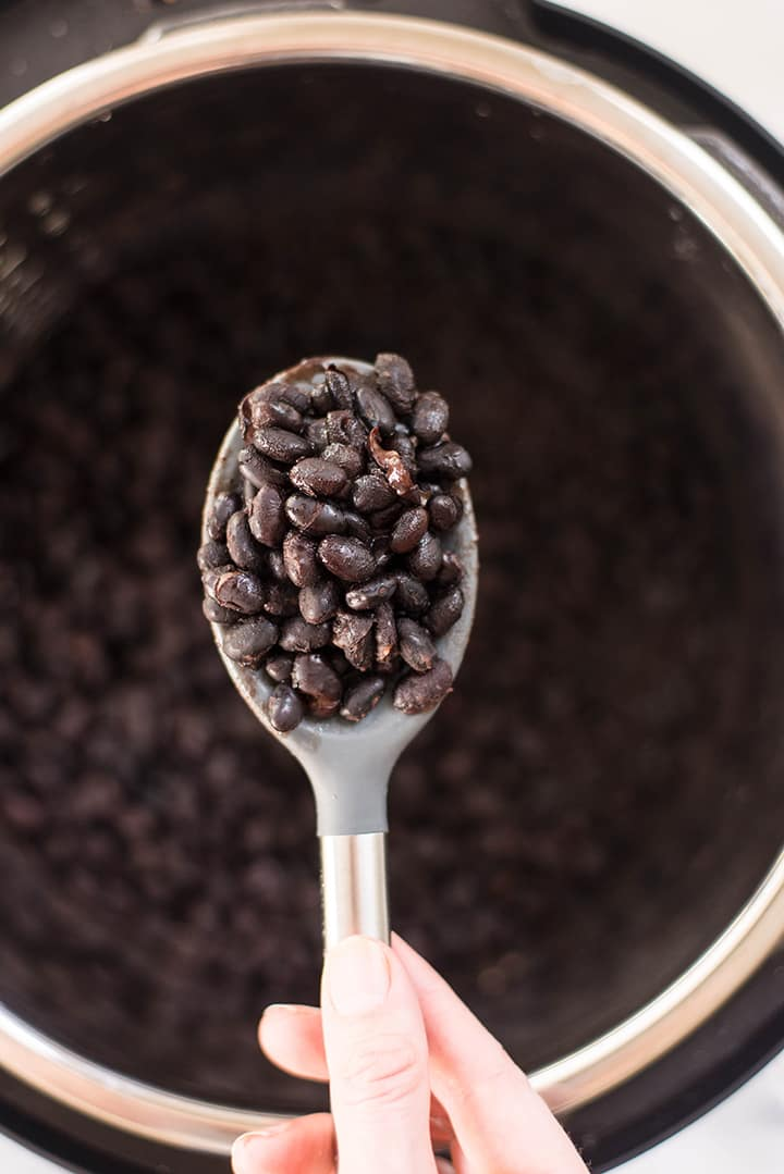 View from the top of the instant pot with black beans with a closeup of a spoon filled with cooked black beans.