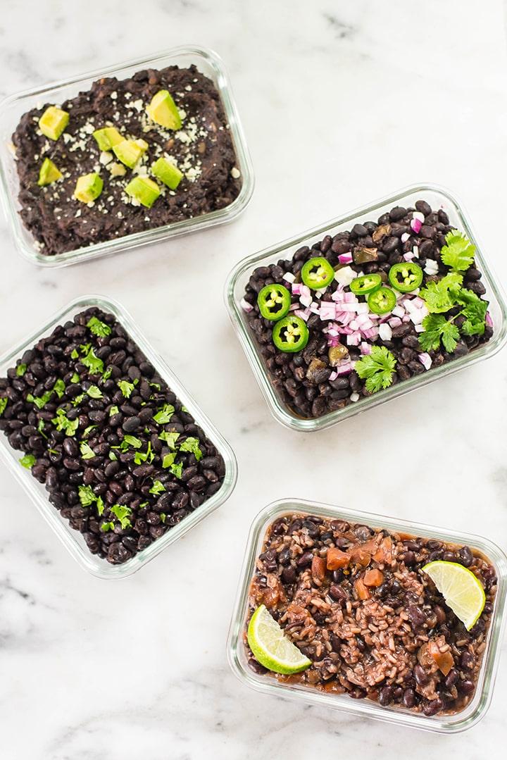 Top view of 4 meal prep containers with plain black beans, Cuban black beans, refried black beans, and black beans with rice cooked in the instant pot.