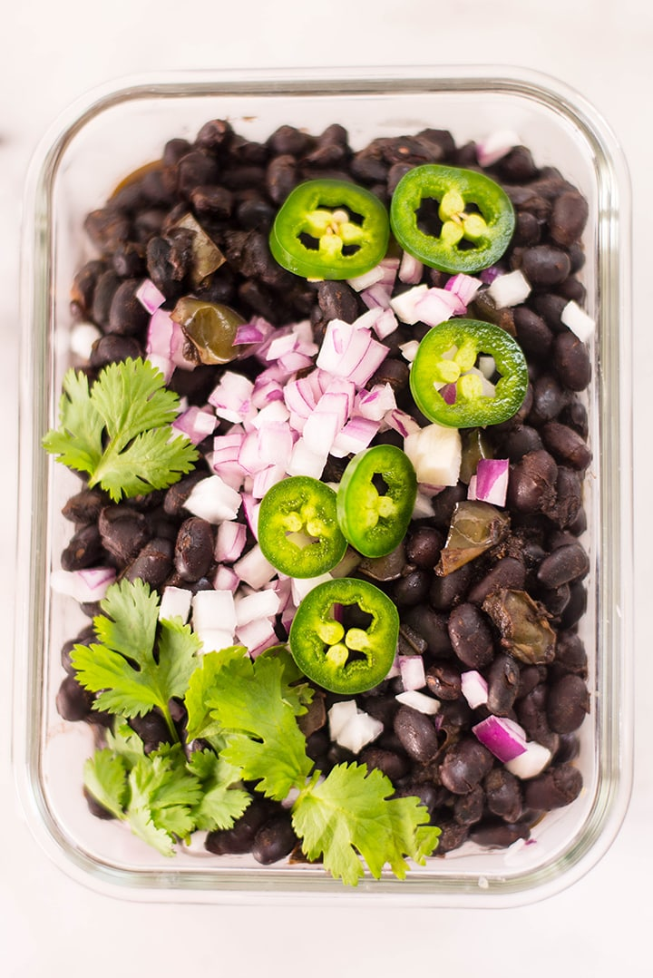 Top view of Cuban black beans in a meal prep container.