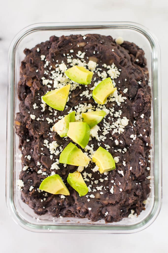 Overhead view of a meal prep container with instant pot black beans topped with avocado.