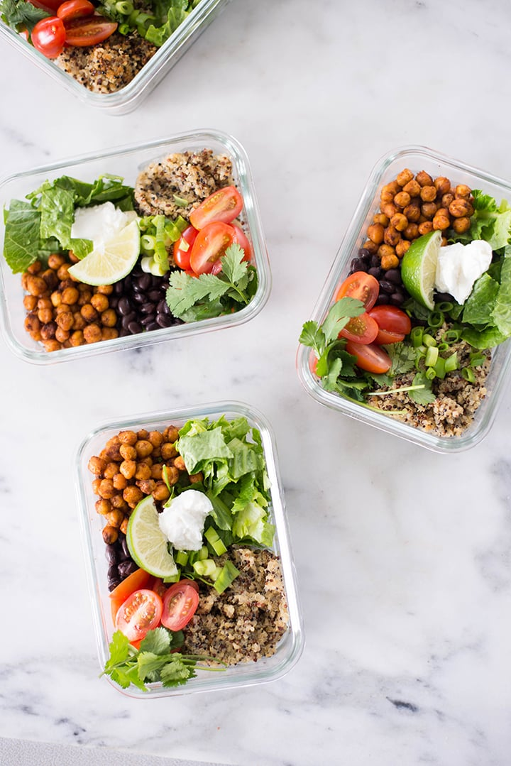 Top view of 4 meal prep containers filled with the prepped ingredients of the Vegetarian Meal Prep Recipe including baked chickpeas, cooked quinoa, fresh veggies, and toppings.