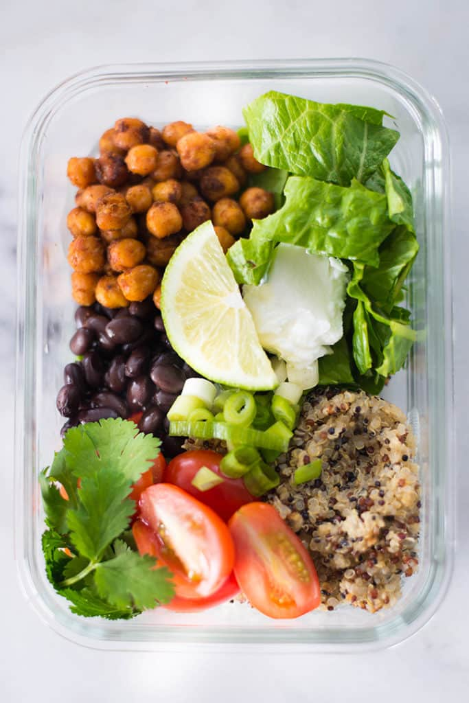 View from the top of a meal prep container filled with the ingredients for the Vegetarian Meal Prep Recipe including baked chickpeas, cooked quinoa, baby greens, grape tomatoes, cilantro, lime slices, and black beans.
