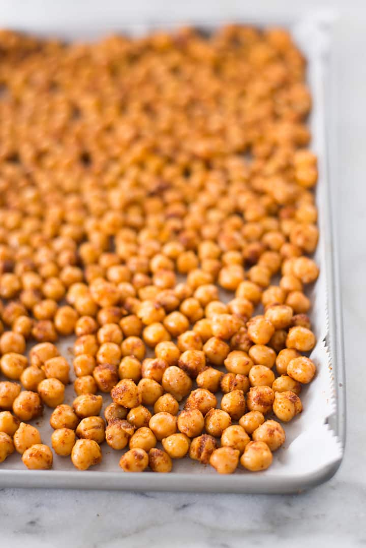 Close up of freshly bake chickpeas on a baking tray lined with parchment paper.