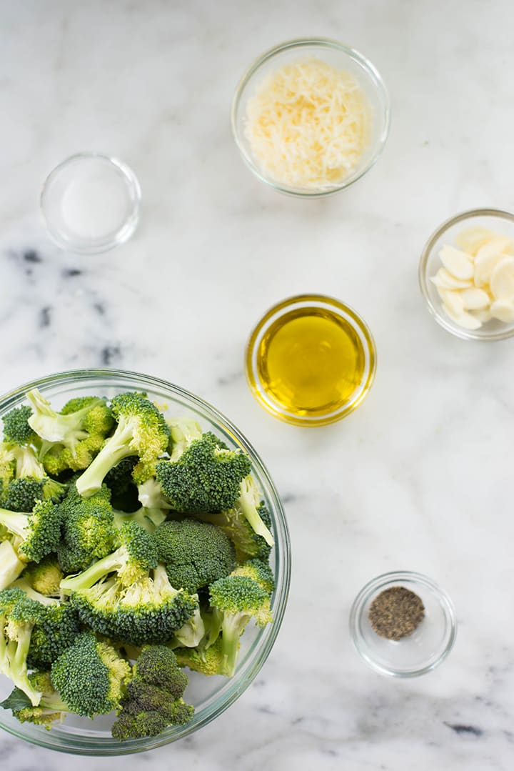 Separate ingredients for the garlic parmesan roasted broccoli including olive oil, garlic, parmesan, salt, and pepper, and garlic cloves.