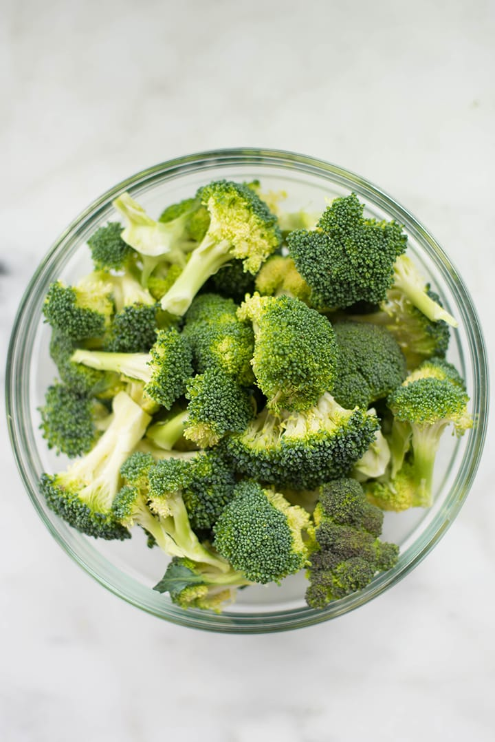 Broccoli florets in a mixing bowl. The florets will be turned into roasted broccoli.