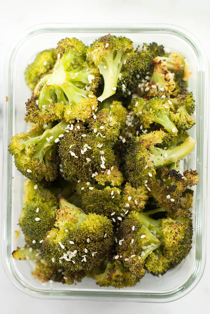Sesame ginger roasted broccoli garnished with sesame seeds in a meal prep container.