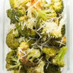 Parmesan garlic roasted broccoli in a meal prep container. The broccoli meal prep was garnished with parmesan.