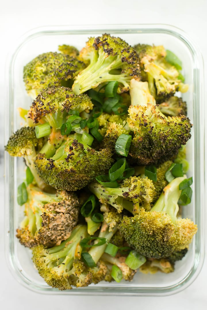 Spicy roasted broccoli garnished with green onions in a meal prep container.