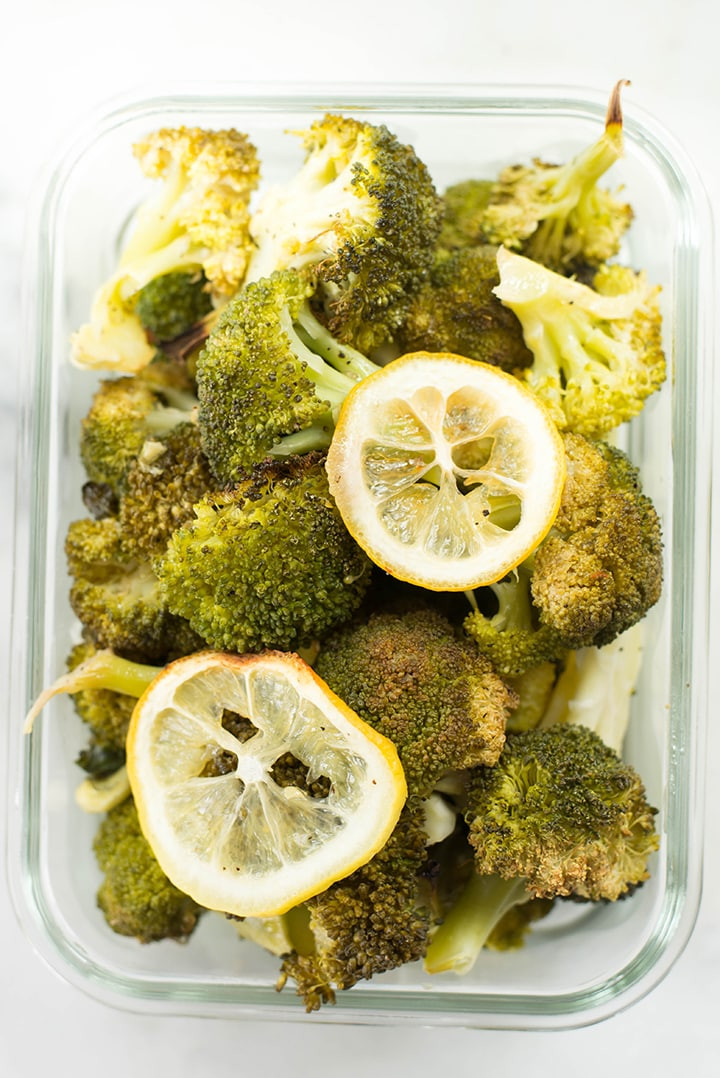 Lemon roasted broccoli garnished with lemon slices in a meal prep container.