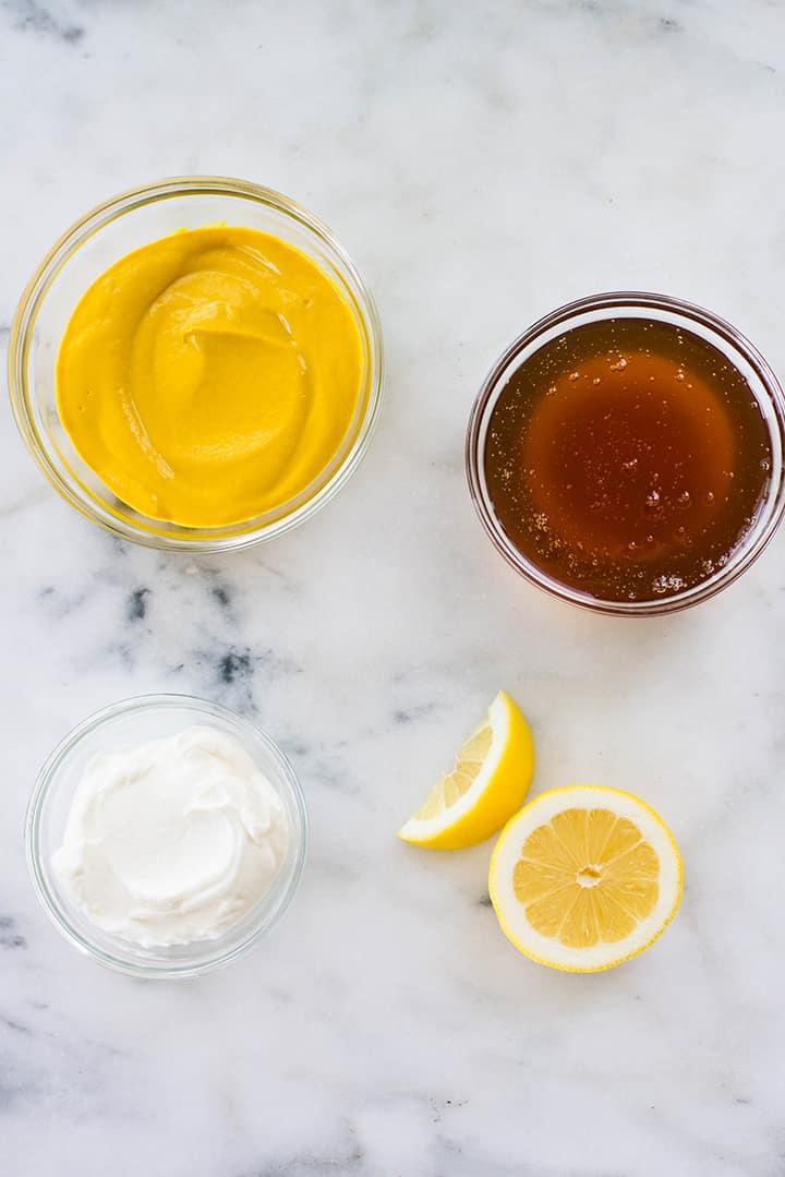 Separated ingredients for Healthy Honey Mustard Dressing including lemon, raw honey, mustard, and greek yogurt.