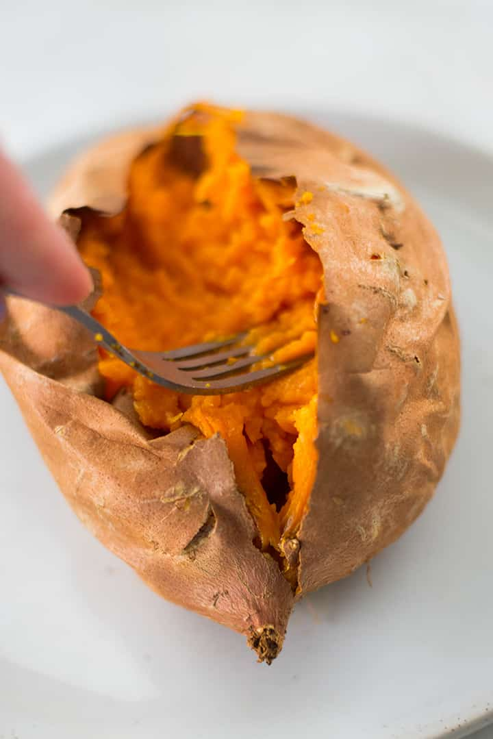 Mashing the inside of a baked sweet potato with a fork to make room for baked sweet potato toppings.