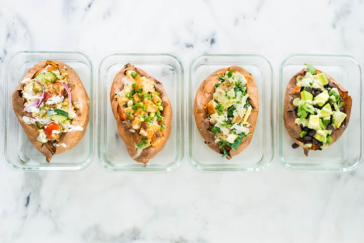 Top view of the 4 different types of baked sweet potatoes including Chipotle Black Beans, buffalo Chicken, Spinach and Artichoke, and Greek Quinoa Salad in meal prep containers.