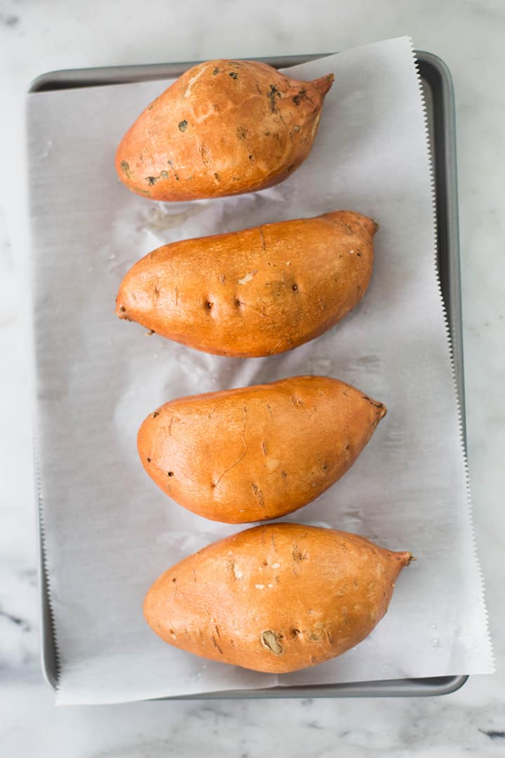 4 medium-large sweet potatoes on a baking sheet lined with parchment paper ready to be transferred to the oven and baked.