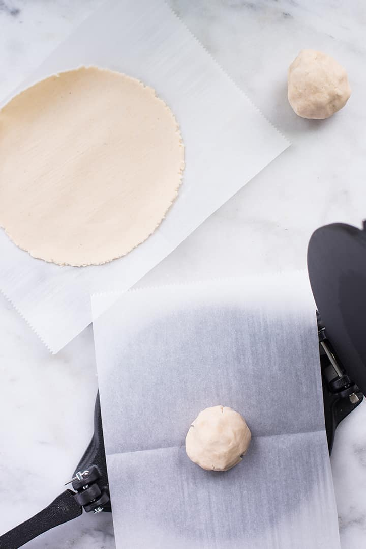 How to make tortillas with tortilla press: step one place cover the tortilla press with parchment paper and place a dough on it, in the middle. Close the the tortilla press can be seen a tortilla that's already been made with the press.