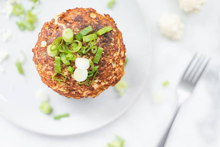 View from the top of a serving plate with cauliflower hash browns. The hash browns are garnished with sliced green onions.