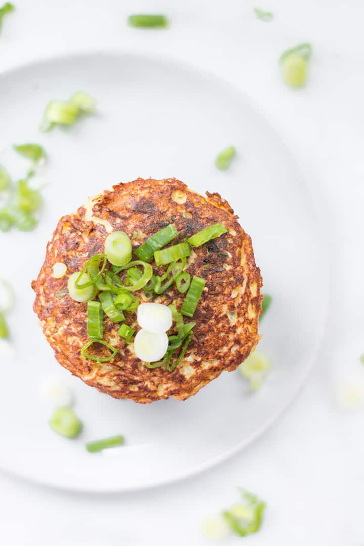 Top view of cauliflower hash browns garnished with green onions on a serving plate.