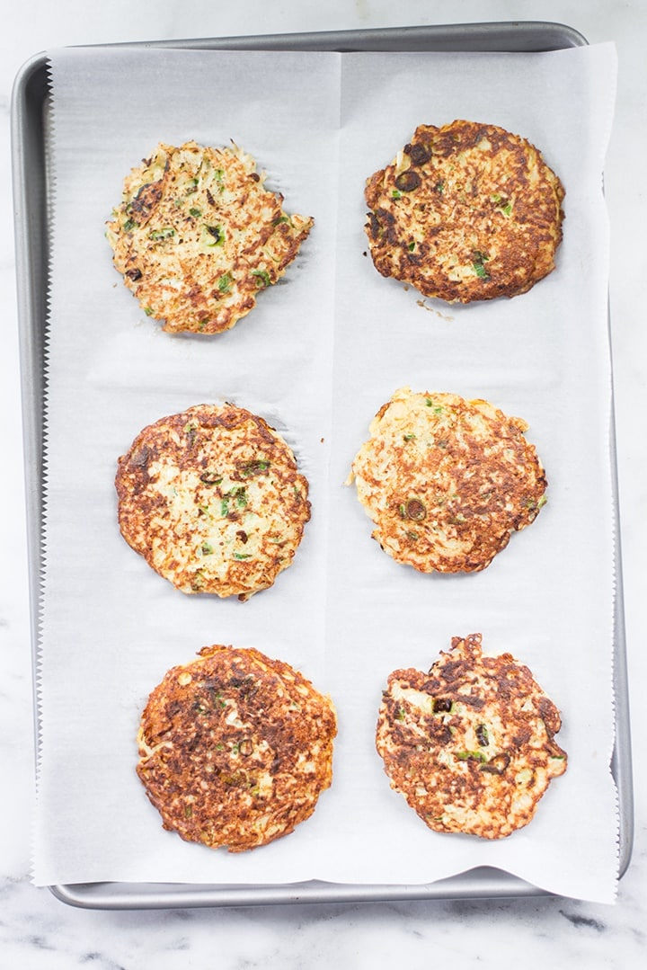 Freshly baked cauliflower hash browns on a baking sheet lined with parchment paper.