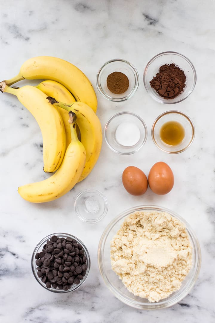 Separated ingredients for healthy chocolate muffins including bananas, eggs, coconut oil, dark chocolate morsels, vanilla extract, ground cinnamon, baking soda, and almond flour.