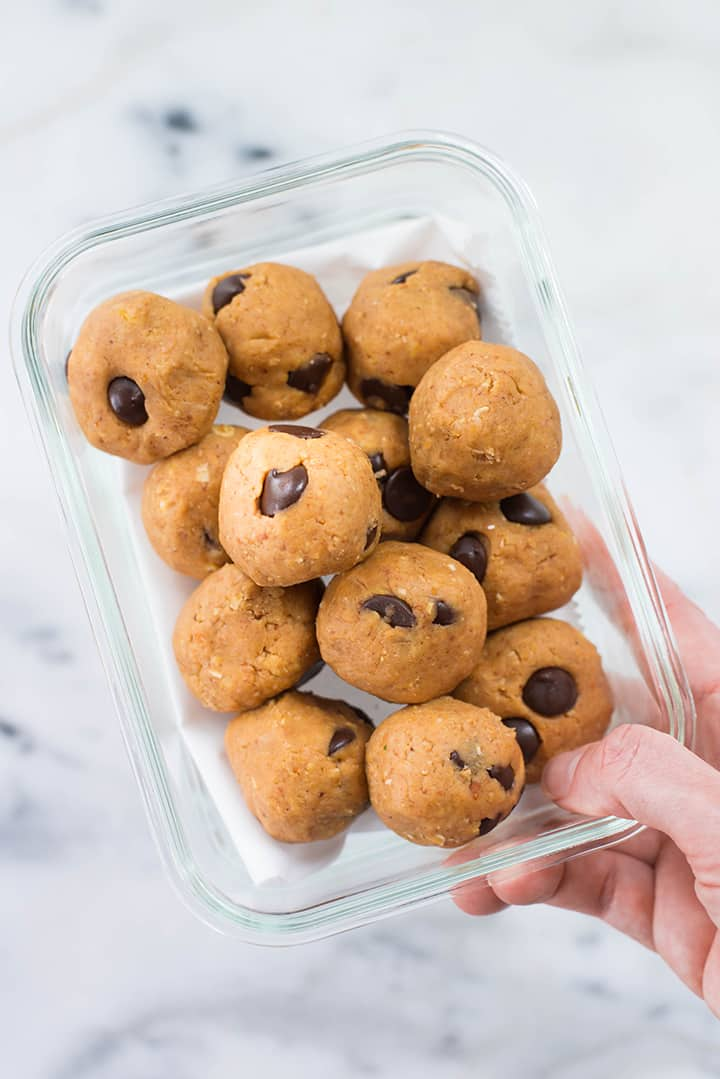 Chocolate Chip Peanut Butter Cookie Dough Bites in a meal prep container ready to be placed in the fridge to store for later.