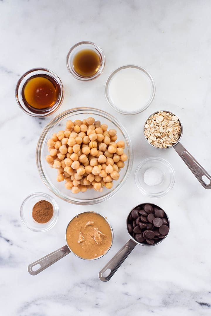Separate ingredients for Chocolate Chip Peanut Butter Cookie Dough Bites including chickpeas, peanut butter, vanilla extract, rolled oats, pure maple syrup, ground cinnamon, sea salt, almond milk, and chocolate chips.