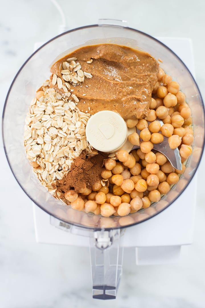 Ingredients for edible cookie dough including chickpeas, peanut butter, maple syrup, vanilla extract, ground cinnamon, rolled oats, sea salt, and almond milk in a food processor.
