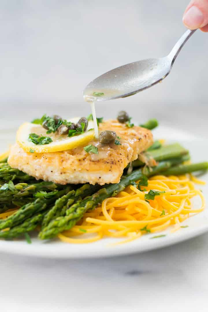 Drizzling saue over halibut picatta served on top of steamed asparagus and chickpea spaghetti.