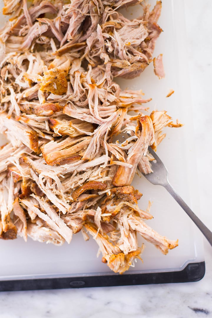 Close up of pulled pork shredded with 2 forks.