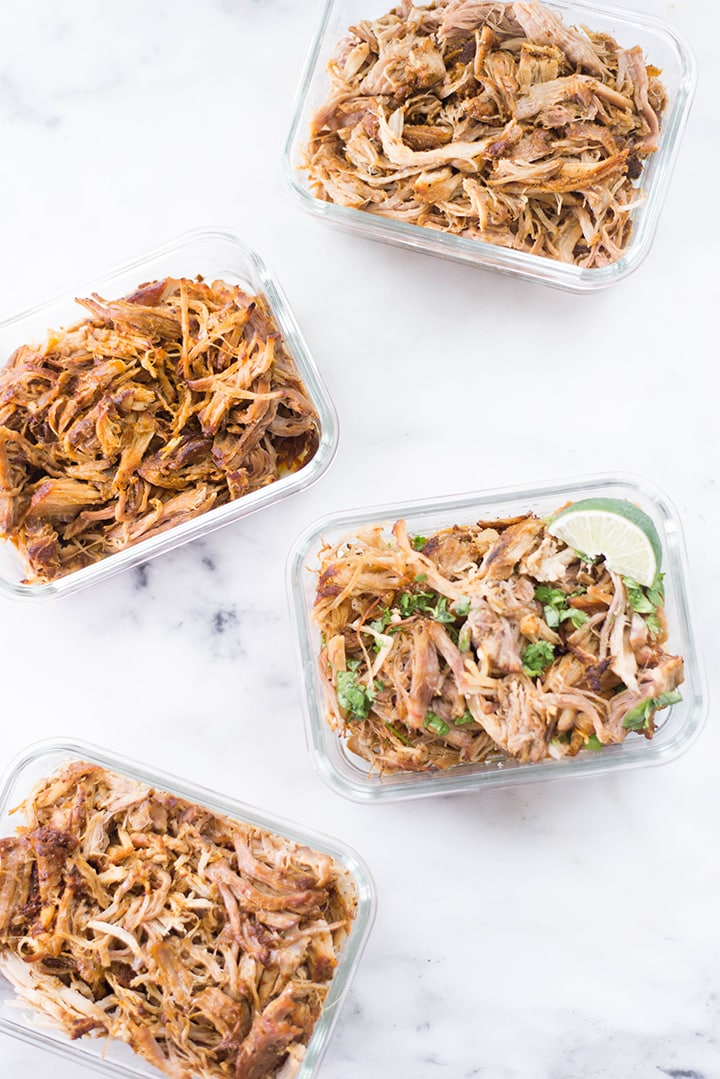Top view of Instant Pot pulled pork in meal prep containers. There are 4 meal prep containers filled with the 4 different types of pulled pork including Basic Pulled Pork, BBQ Pulled Pork, Carolina Pulled Pork, and Carnitas Pulled Pork.